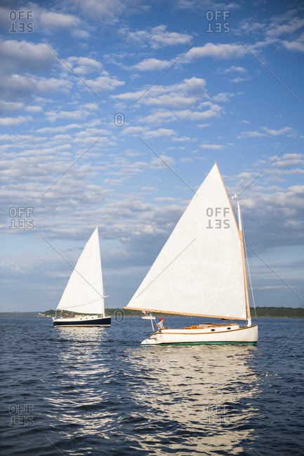 Two catboat sailboats sailing during golden hour sunset in summer