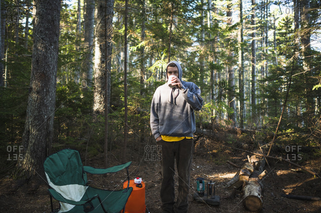 Solo man drinking coffee while camping in coastal maine