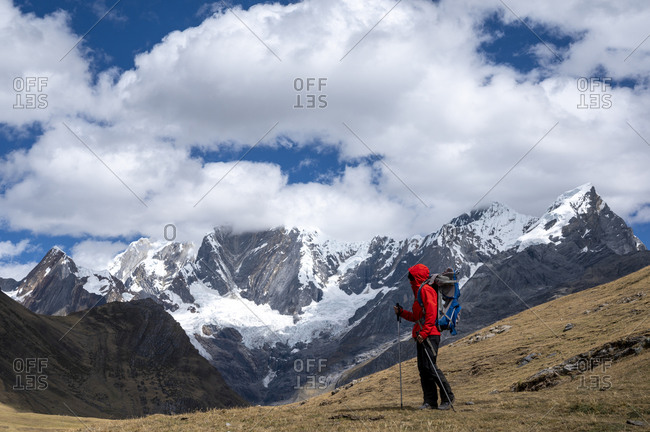 One person with poles hiking along the huayshuash circuit in peru