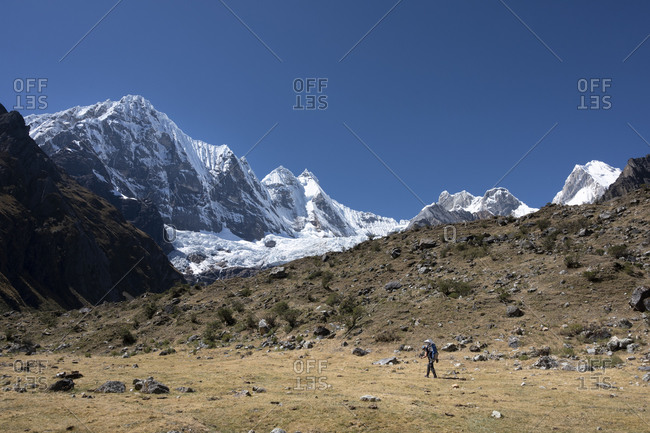 A mom hiking with her son on a backpack at high altitud with mountains