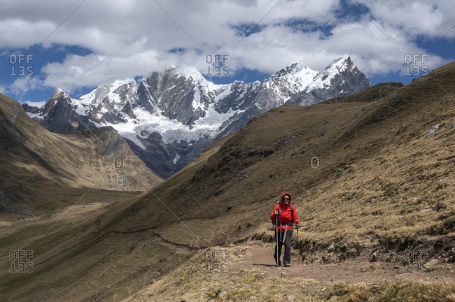 One person using poles hikes on a trail at cordillera huayhuash