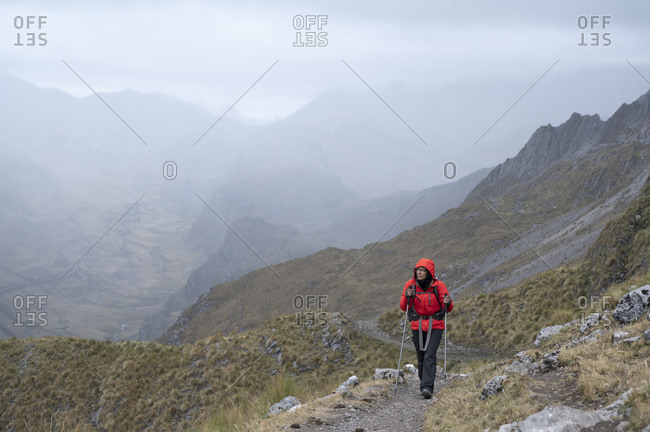 One person with poles hiking on a trail at cordillera huayhuash