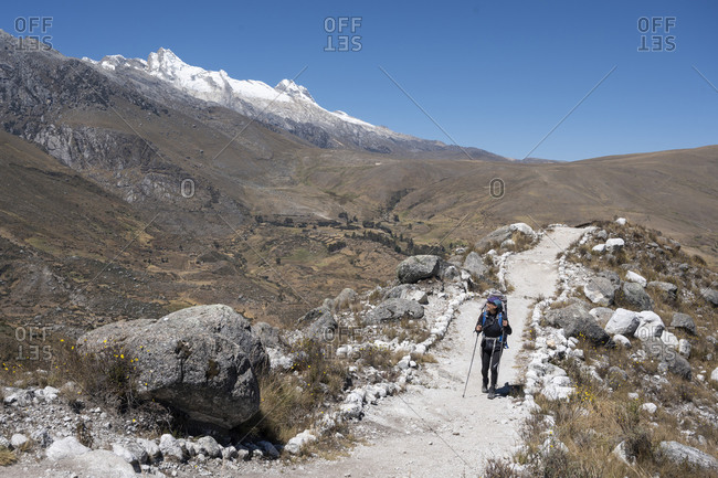 One woman with backpack and poles hiking at cordillera blanca