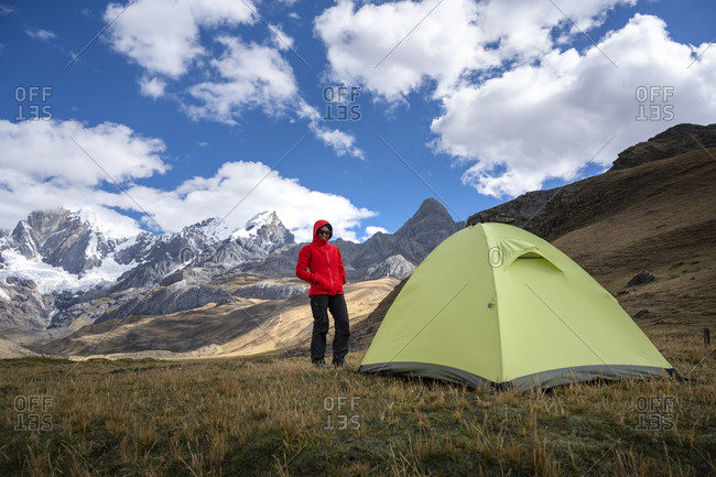 One woman standing at a high altitud camp next to a tent in huayhuash