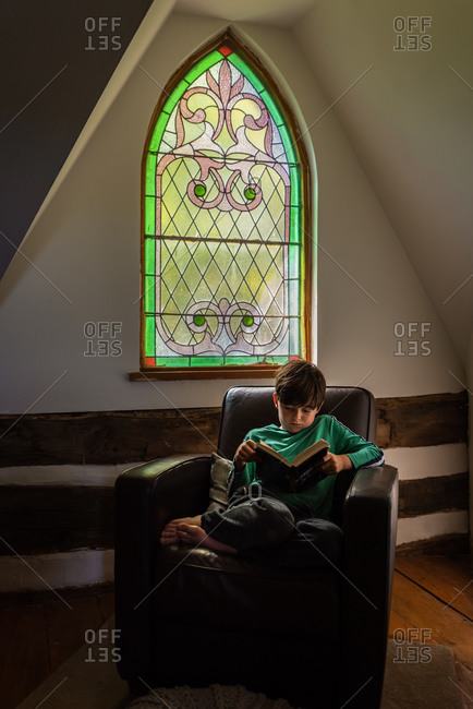 Young boy reading in leather chair in front of ornate window of home.