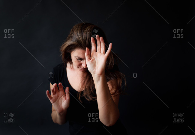 Woman with long brown hair reaching her hands out in darkened room.