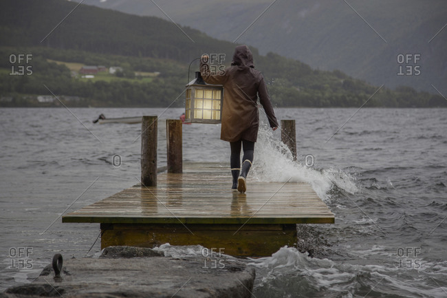 A person carrying a lantern on a dock in the rain