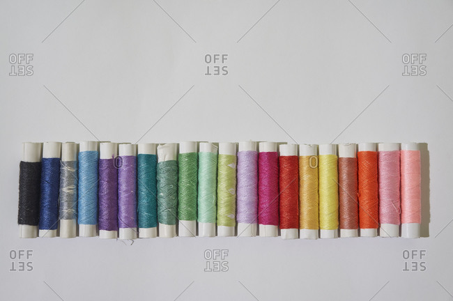 Top view of colorful spools of thread on white background.