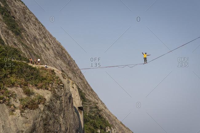 Niteroi, rj, brazil - september 18, 2020: beautiful view to highliner walking the line on rocky ocean shore