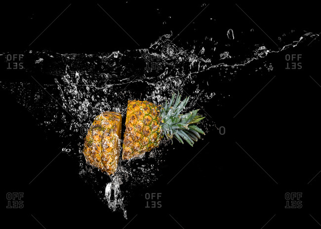 Pineapple falling into water with bubbles on black background