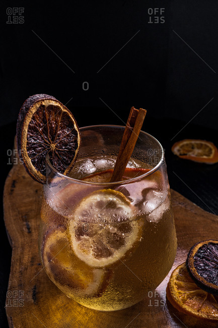 Gin tonic cocktail with cinnamon and lemon on a wooden table