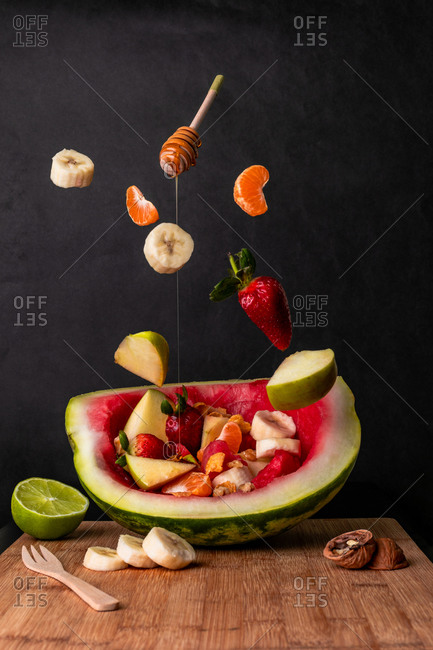 Composition of flying fruits falling on a bowl-shaped watermelon dippe