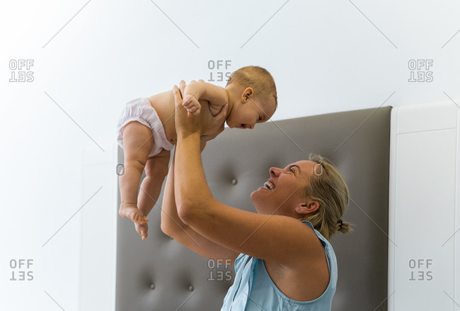 Mom playing with the baby lifting it very high