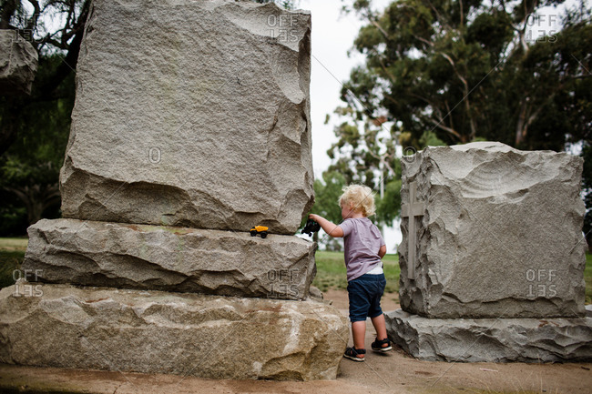 Two year old standing between headstones at park