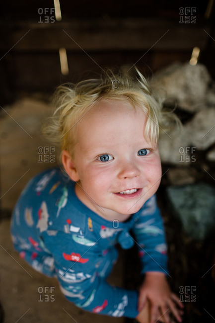 Close up of two year old smiling for camera sitting in front yard