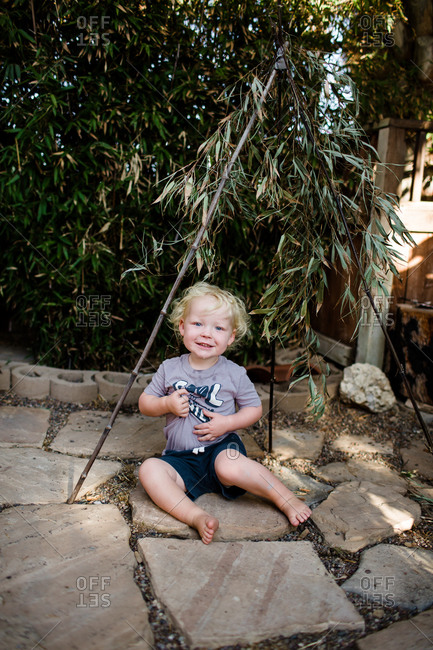 Two year old boy sitting under bamboo smiling for camera
