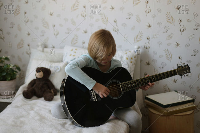 A russian girl plays a musical instrument in her room.