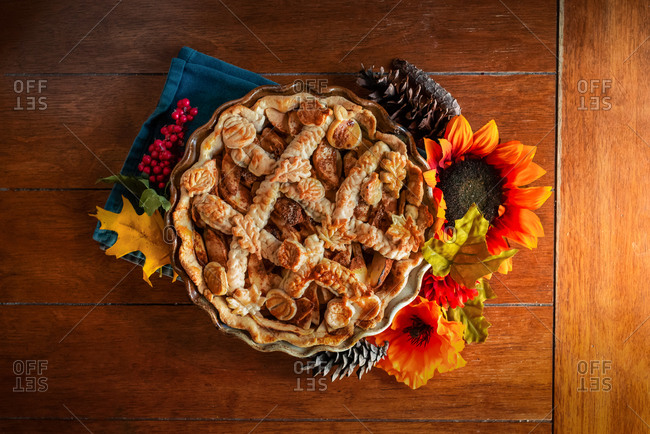 Apple pie decorated with fall seasonal props on a kitchen table