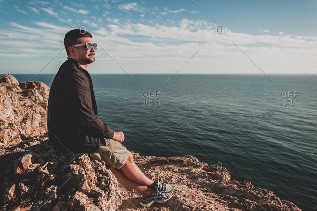 Young man looking out over ocean at sunset in portugal in summer
