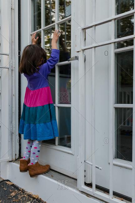 Little girl impatiently waiting at door in dress