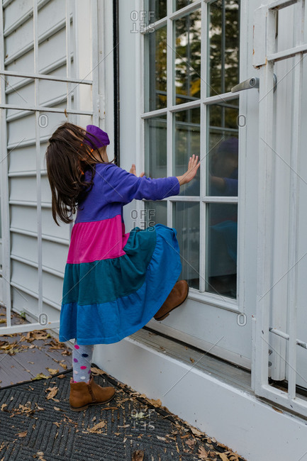Little girl waiting at door with face mask, impatient