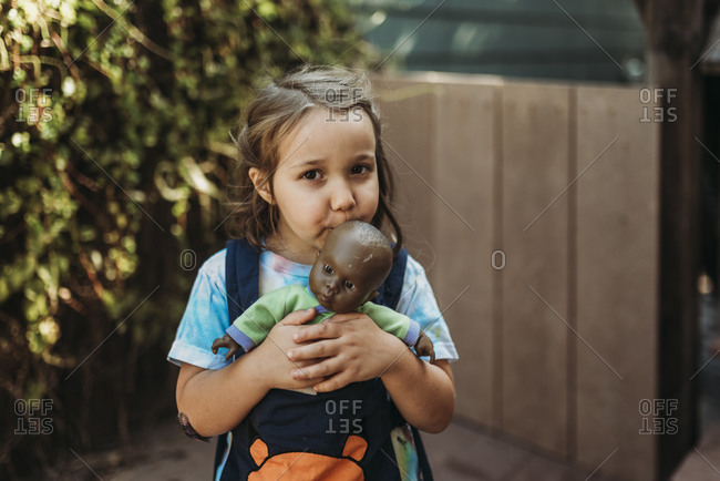 Young girl kissing favorite baby doll outside in yard