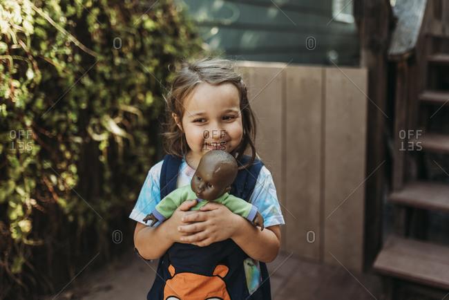 Preschool age girl cuddling baby doll outside on deck