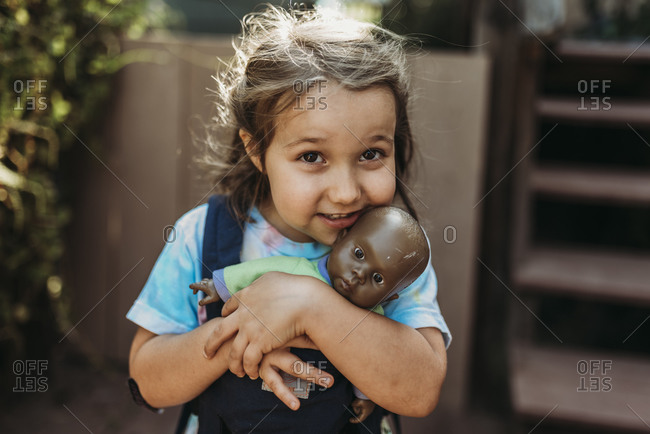 Close up of young girl cuddling with favorite baby doll outside