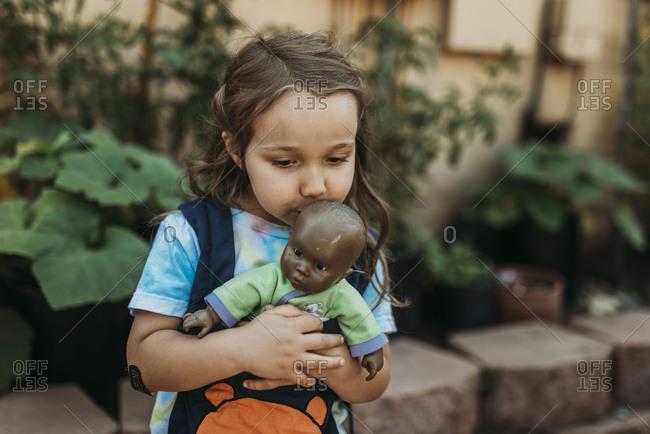 Preschool aged girl carrying babydoll in baby carrier in garden