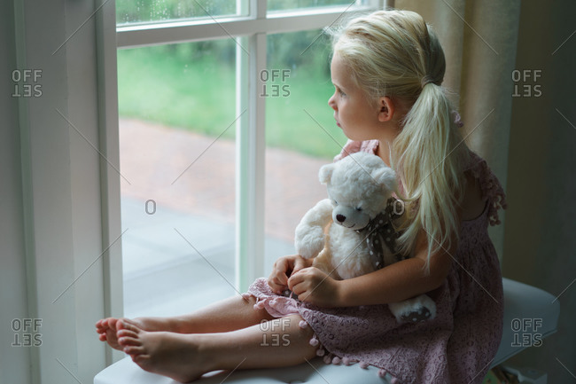 Little girl looking sadly out the window watching rain.