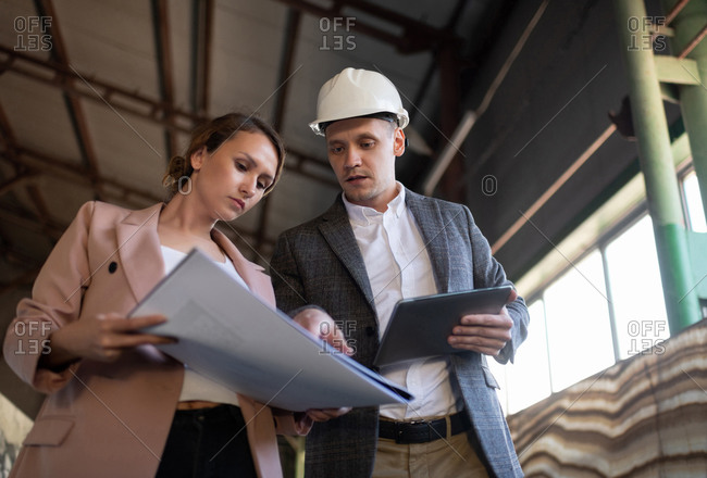 Contemporary engineers examining draft in warehouse building