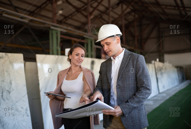 Professional entrepreneurs with blueprint in stone company manufacture