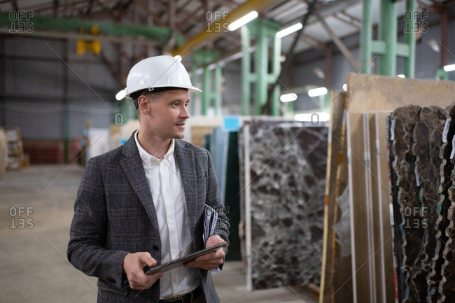 Businessman picking materials in stone warehouse