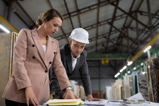 Focused coworkers examining blueprint in warehouse