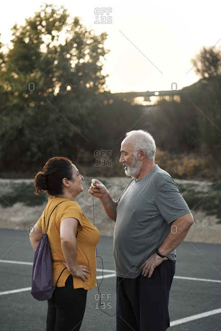 An elderly couple is sharing a headset for sport