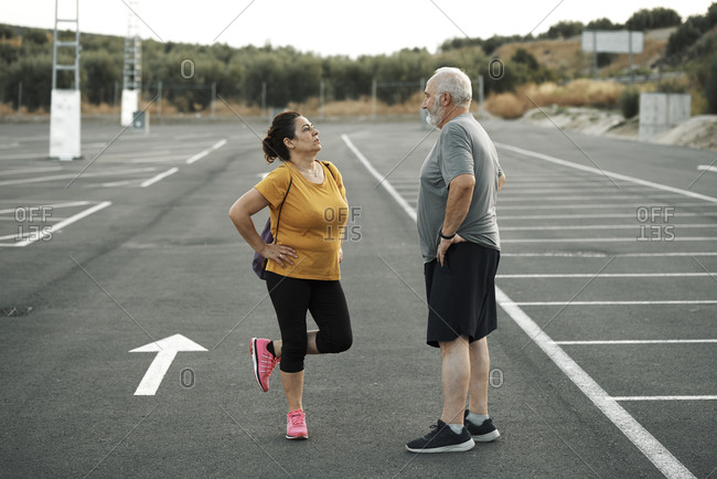 A middle-aged man and woman get ready to exercise