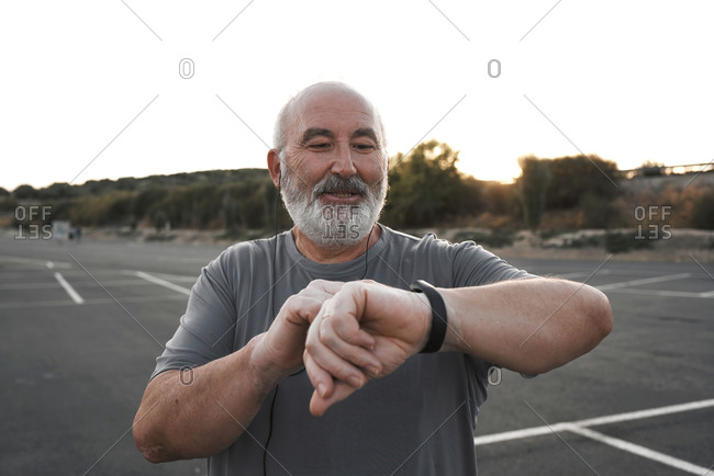 An old man with white hair and beard is looking at his smart watch