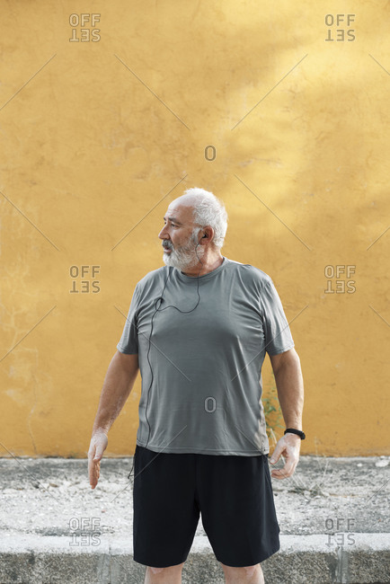 An overweight older man is ready to stretch