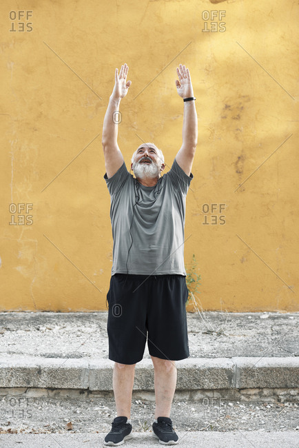 An overweight older man is stretching in front of a wall
