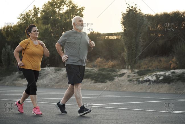 A woman and an elderly man are jogging in the street