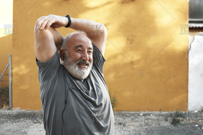 An old man is stretching out his arm with a sore face