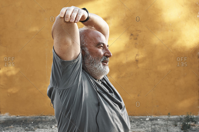 An older man with white hair and beard is stretching his arm