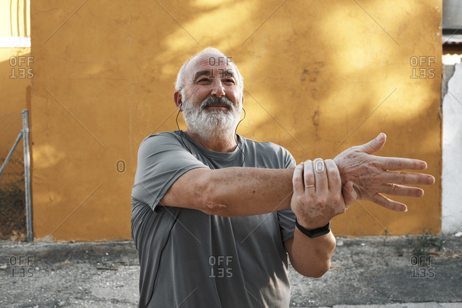 An elderly man with white hair and beard is stretching outdoors