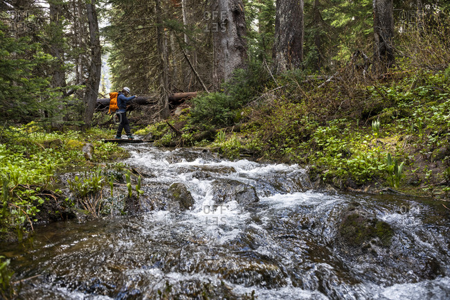 Hiker with backpack crossing fast flowing stream in mountain forest