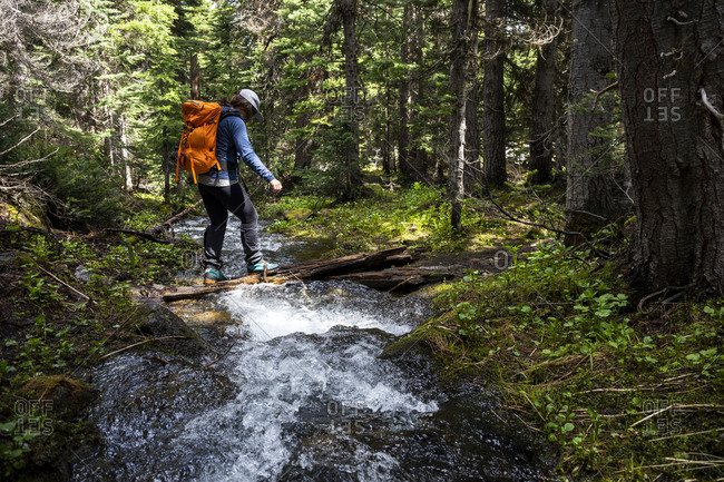 Side view of unrecognizable hiker with backpack crossing narrow fast stream flowing through green woods in mountainous region