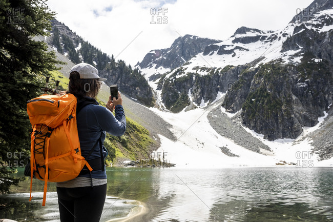 Female hiker with backpack and smartphone standing near lake and photographing picturesque landscape of snowy rocky mountains during summer journey in British Columbia