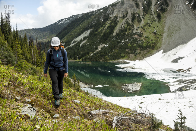 Full body of female hiker walking on shore of lake surrounded by snowy mountains and green forest on summer day in canada