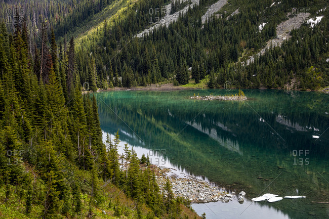 Calm lake reflecting mountain slopes with green forest on summer day