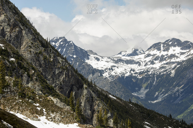 Wild landscape of rocky mountains covered with snow under cloudy sky