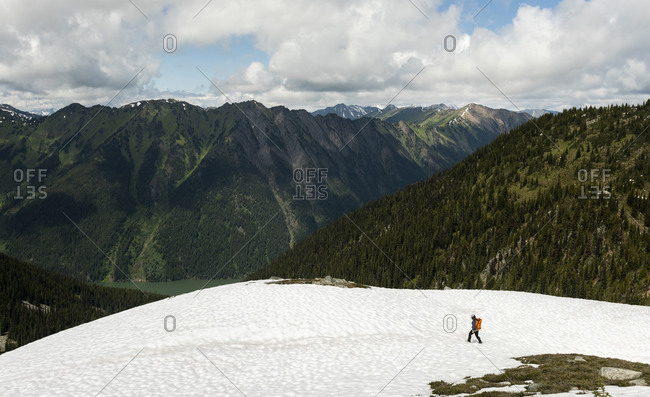 From above side view of anonymous explorer with backpack walking on snowy hilltop against majestic forested mountains in cloudy day